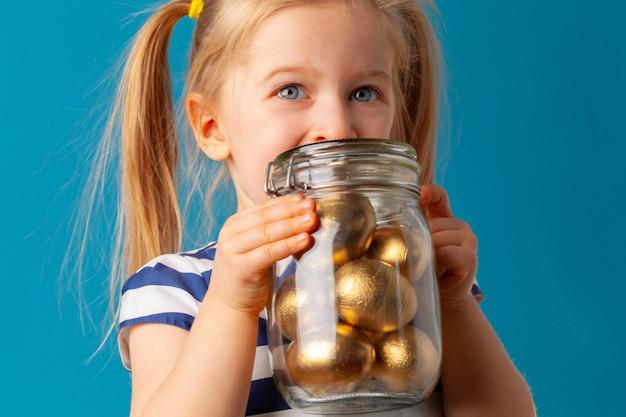 Menina bonita, segurando o frasco de vidro com ovos de ouro coloridos para a páscoa
