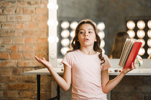 Menina bonita segurando o livro ensaiando nos bastidores