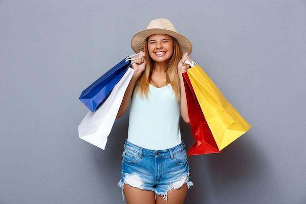 Menina bonita segurando sacolas coloridas sobre fundo cinza.