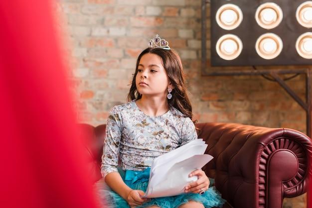 Menina bonita segurando scripts sentado no sofá olhando para longe