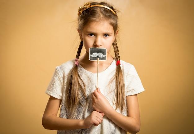 Menina bonita segurando um bigode decorativo engraçado