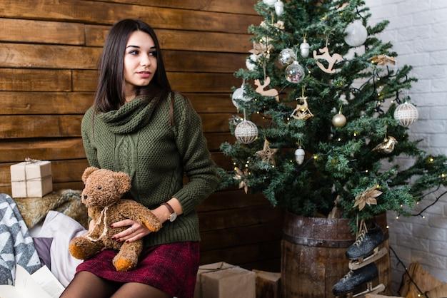 Menina bonita segurando um ursinho de pelúcia em uma atmosfera de natal