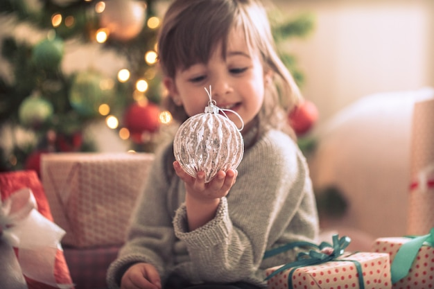 Menina bonita segurando uma caixa de presente e sorrindo enquanto está sentada na cama no quarto de casa