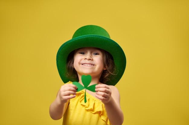 Menina bonita segurando uma folha de trevo nas mãos e mostra-a para a câmera