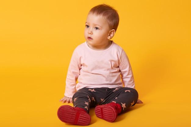 Menina bonita senta-se no chão, camisola vestida