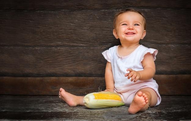 Menina bonita senta-se sobre um fundo escuro de madeira e mastiga seda de milho.