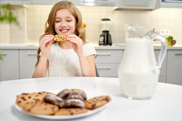 Menina bonita sentada à mesa, comendo biscoitos com passas.