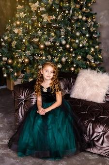 Menina bonita sentada ao lado da árvore de natal. pequena princesa em trajes elegantes, cabelo longo e encaracolado, tema de ano novo.