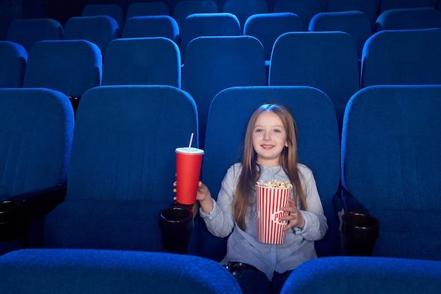 Menina bonita sentada com balde de pipoca no cinema.