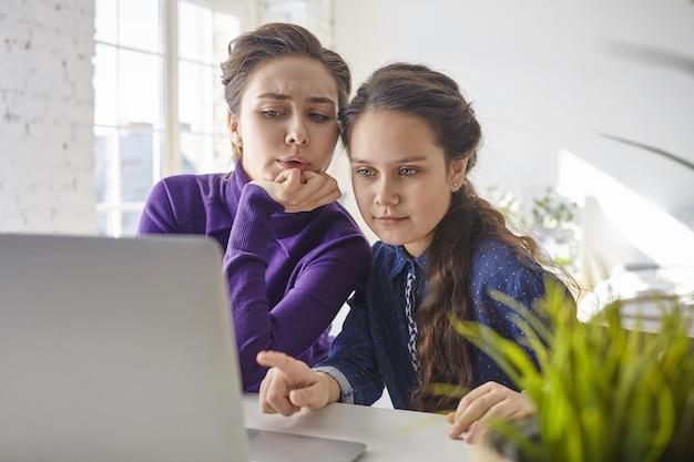 Menina bonita sentada em frente a um computador portátil aberto em casa, apontando o dedo para a tela, a mãe ao lado dela se sentindo insegura e chocada