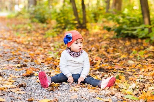 Menina bonita sentada em uma pilha de folhas amarelas.