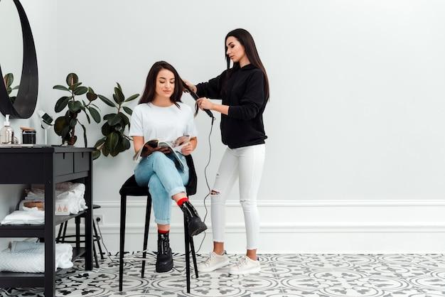 Menina bonita sentada na cadeira de cabeleireiro, lendo revista, seu mestre fazendo penteado