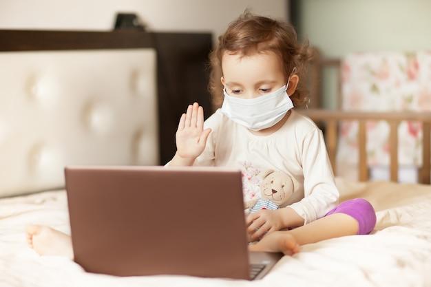 Menina bonita sentada na cama e usando um notebook laptop tablet digital. ligue para amigos ou pais.