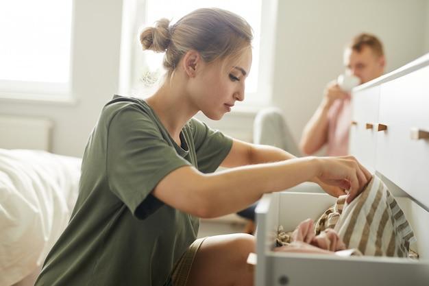 Menina bonita sentada na gaveta aberta enquanto procurava roupas novas