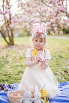 Menina bonita sentada na grama perto da magnólia. uma garota vestida como um coelhinho da páscoa segura uma flor e um ovo. primavera.