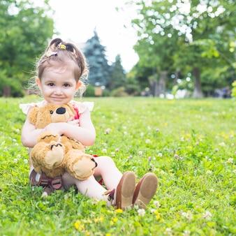 Menina bonita sentada na grama verde, abraçando seu ursinho de pelúcia