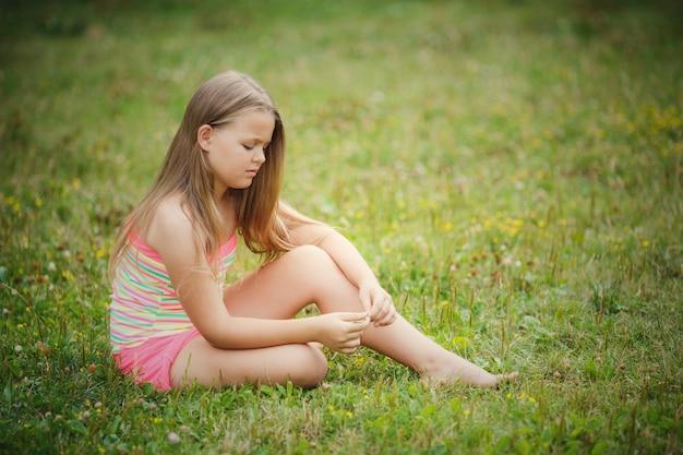 Menina bonita sentada na grama verde ao ar livre