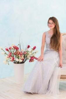 Menina bonita sentada na poltrona perto de vaso de flor olhando para a câmera