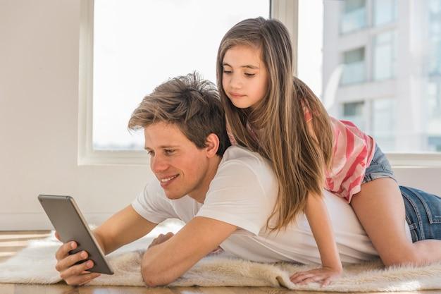 Menina bonita sentada nas costas do pai dela usando telefone celular