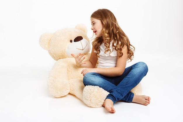Menina bonita sentada no chão com urso de brinquedo, contando a história.