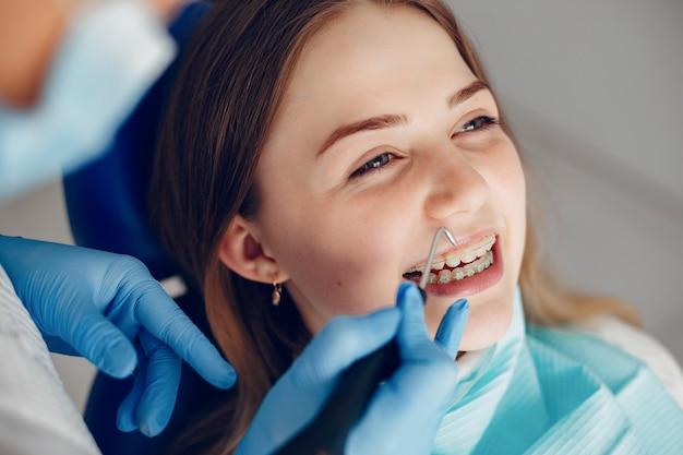 Menina bonita sentada no consultório do dentista