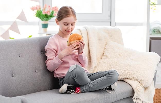 Menina bonita sentada no sofá com hambúrguer nas mãos e olhando para ele