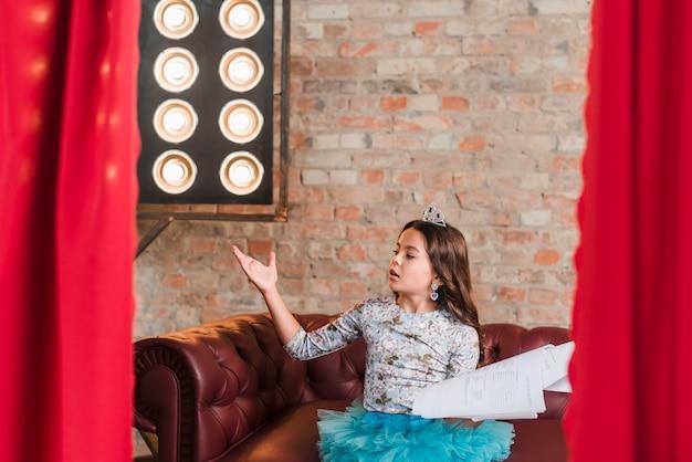 Menina bonita sentada nos bastidores ensaiando