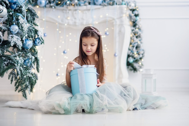 Menina bonita sentada perto de árvore de natal dentro de casa.