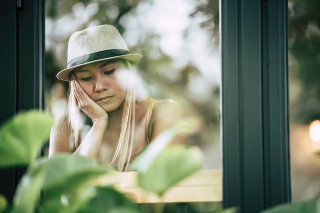 Menina bonita sentada triste na janela no café