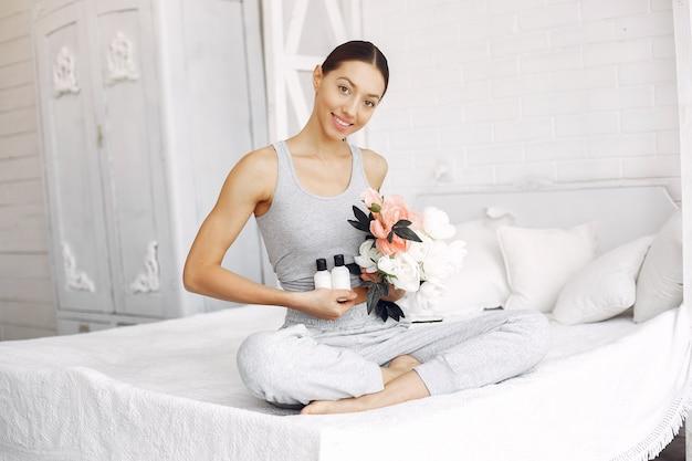 Menina bonita, sentado em uma cama com produtos de beleza