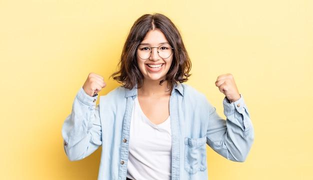 Menina bonita sentindo-se feliz, positiva e bem-sucedida, comemorando a vitória, conquistas ou boa sorte
