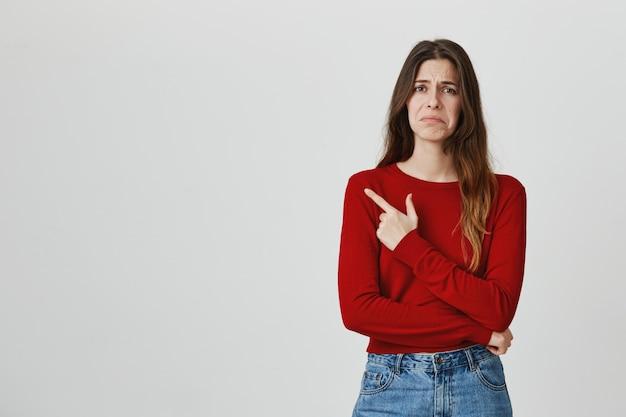 Menina bonita sombria desapontada, apontando o dedo no canto superior esquerdo, fazendo uma careta