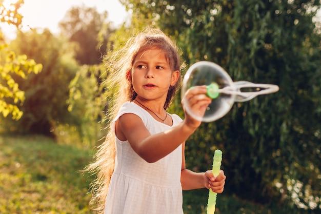 Menina bonita, soprando bolhas no parque primavera. garoto se divertindo jogando jogos ao ar livre.