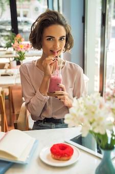 Menina bonita sorridente bebendo batido com um canudo