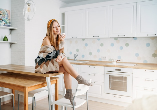 Menina bonita sorridente cabelo comprido justo jovem vestindo no aconchegante casaco de malha com xícara de café da manhã sentado na mesa da cozinha em casa