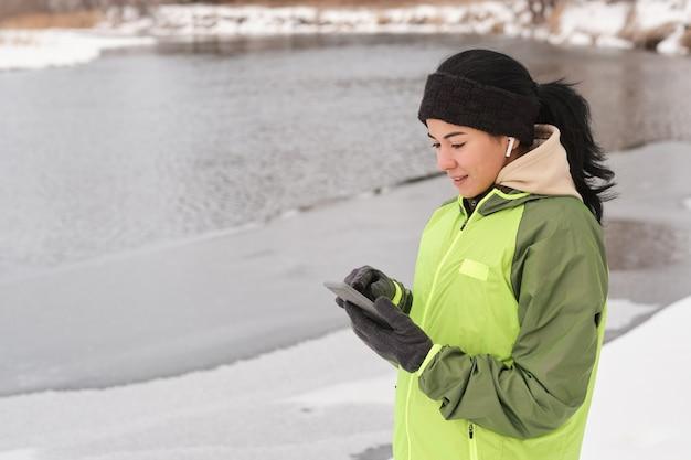 Menina bonita sorridente com bandana em pé na costa de inverno e mensagem de texto no telefone
