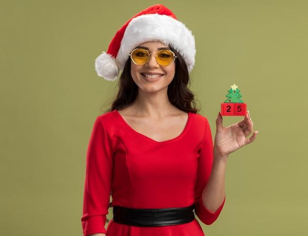 Menina bonita sorridente com chapéu de papai noel e óculos segurando um brinquedo da árvore de natal com um par