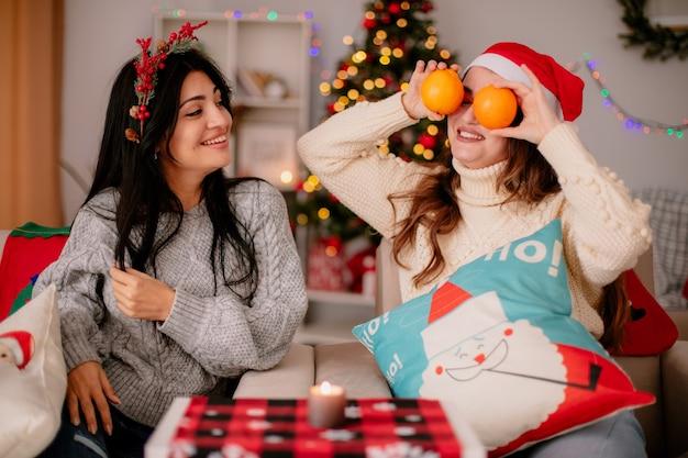 Menina bonita sorridente com coroa de azevinho olha para a amiga c