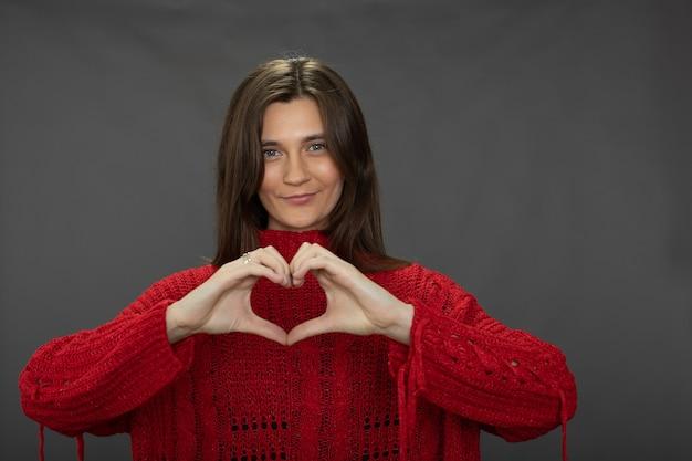 Menina bonita sorridente com suéter vermelho fazendo gesto de coração olhando para frente Foto Premium