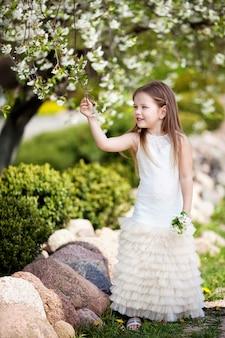 Menina bonita sorridente com vestido creme no jardim de flores