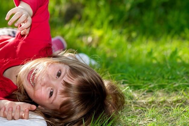 Menina bonita sorridente criança bonita com olhos cinzentos e cabelos louros longos se divertindo ao ar livre, deitado na grama verde no campo ensolarado verde verão turva. beleza, sonhos e jogos de infância.