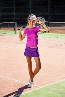 Menina bonita sorridente de uniforme com raquete de tênis no ombro em pé na quadra de tênis ao ar livre ao pôr do sol.