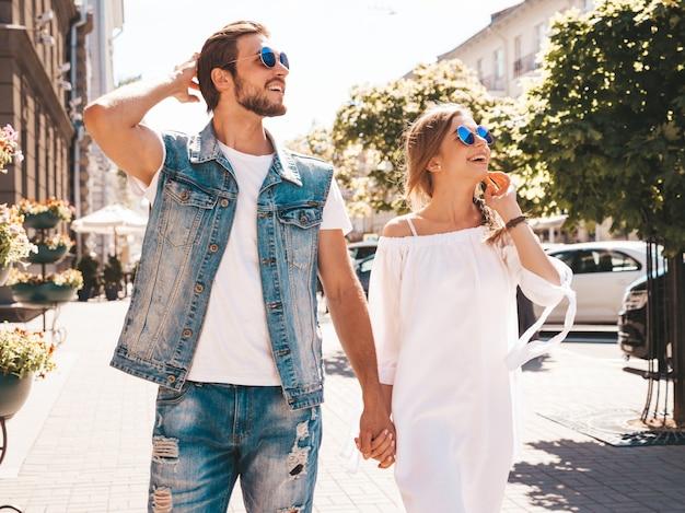 Menina bonita sorridente e seu namorado bonito andando na rua.