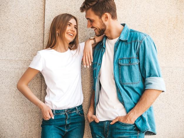 Menina bonita sorridente e seu namorado bonito em roupas de verão casual. família alegre feliz se divertindo no fundo da rua. olhando um para o outro