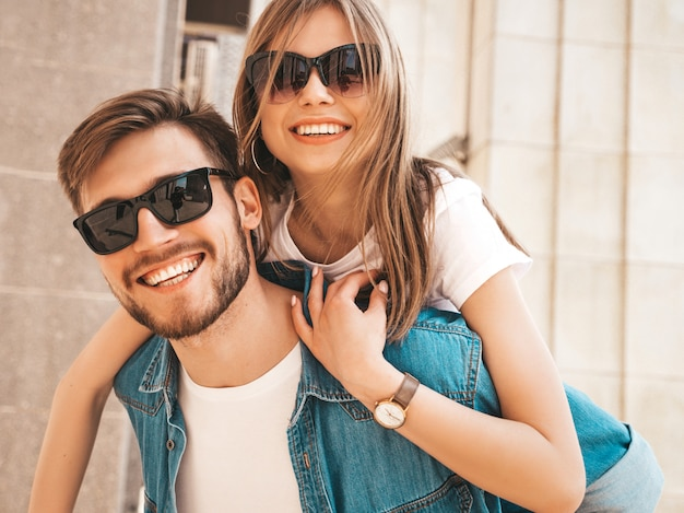 Menina bonita sorridente e seu namorado bonito em roupas de verão casual. homem carregando sua namorada nas costas e ela levantando as mãos.