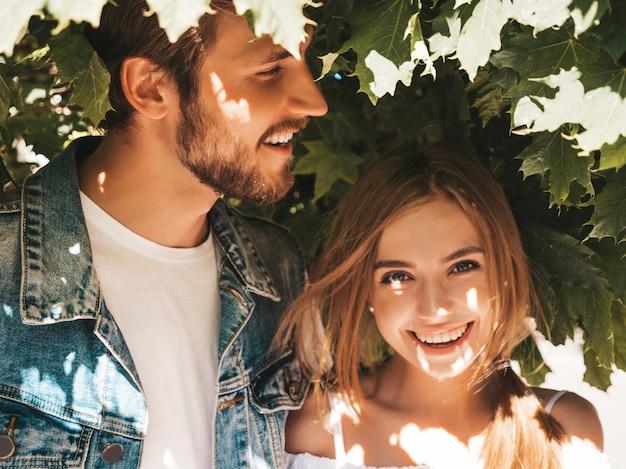 Menina bonita sorridente e seu namorado bonito posando na rua perto de árvore.