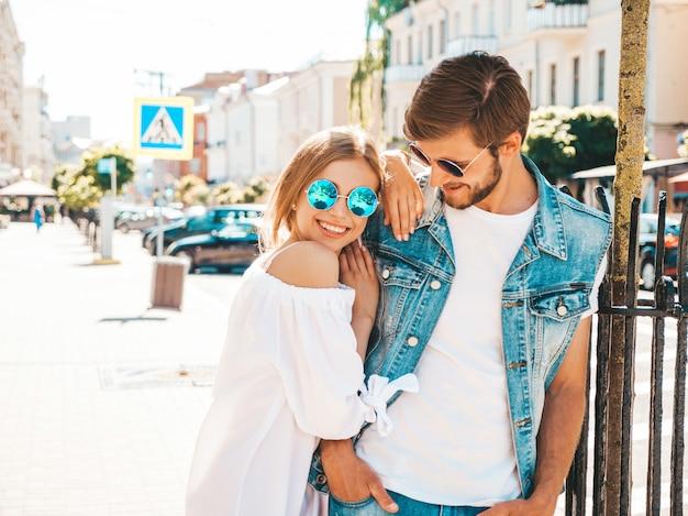 Menina bonita sorridente e seu namorado bonito posando na rua.