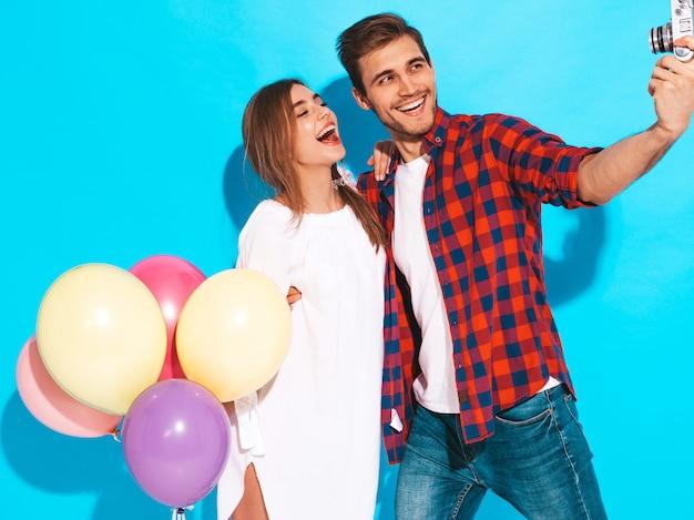 Menina bonita sorridente e seu namorado bonito segurando o monte de balões coloridos. casal feliz tirando foto de si mesmo. feliz aniversário