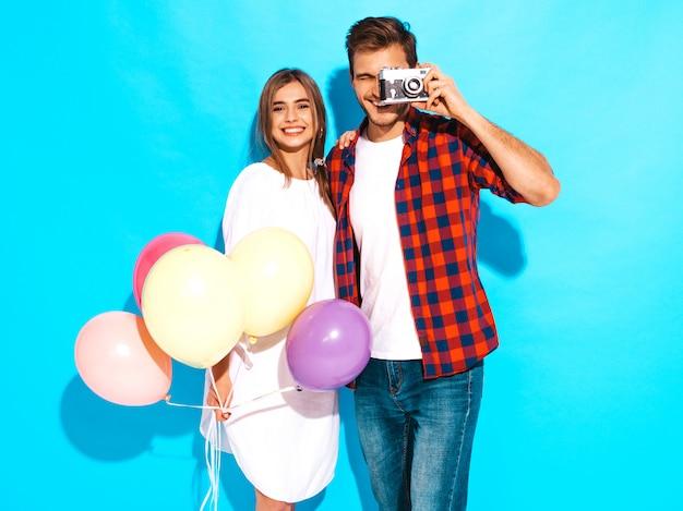 Menina bonita sorridente e seu namorado bonito segurando o monte de balões coloridos. casal feliz tirando foto de si mesmo na câmera retro. feliz aniversário