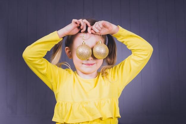 Menina bonita sorridente em camisas amarelas, segurando bolas de natal amarelas brilhantes perto dos olhos e sobre fundo cinza de madeira.